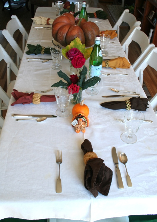 Thanksgiving table setting with antique linen, pumpkin and roses